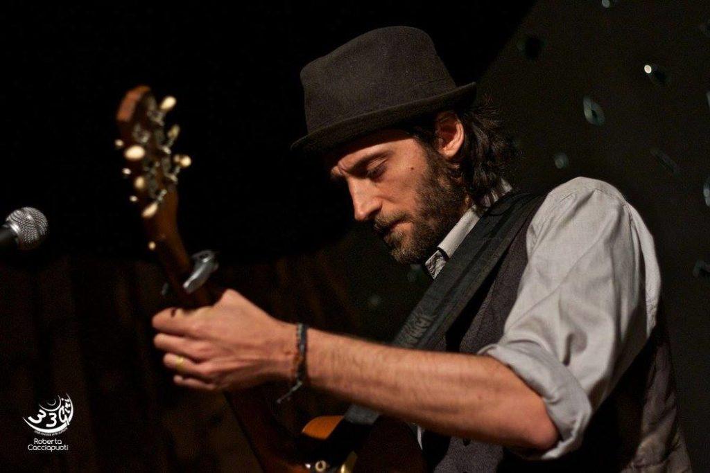 Cantautore con chitarra e cappello